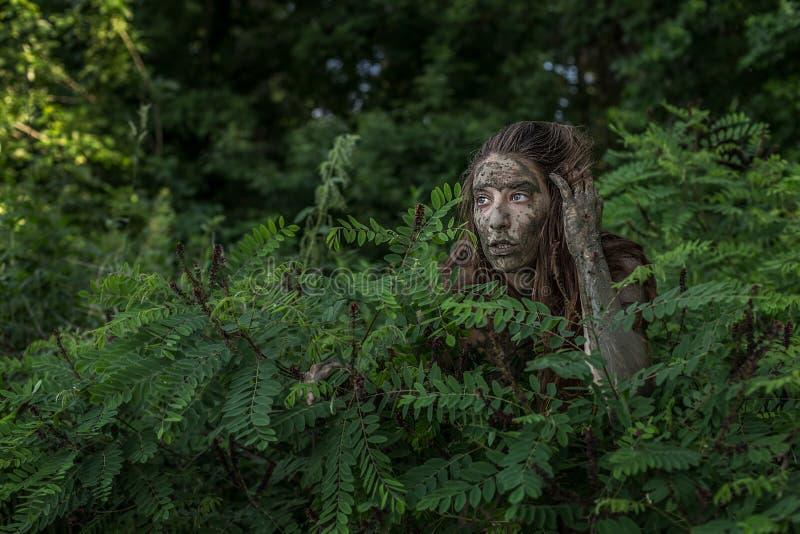 Muchacha de Muddy Amazon que oculta detrás de un arbusto en el bosque fotos de archivo