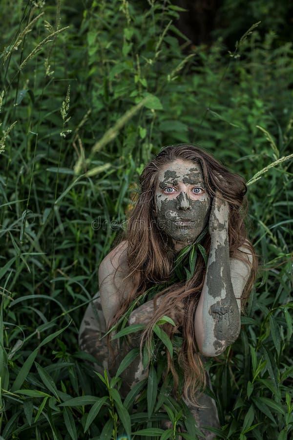 Muchacha de Muddy Amazon que oculta detrás de un arbusto en el bosque imágenes de archivo libres de regalías