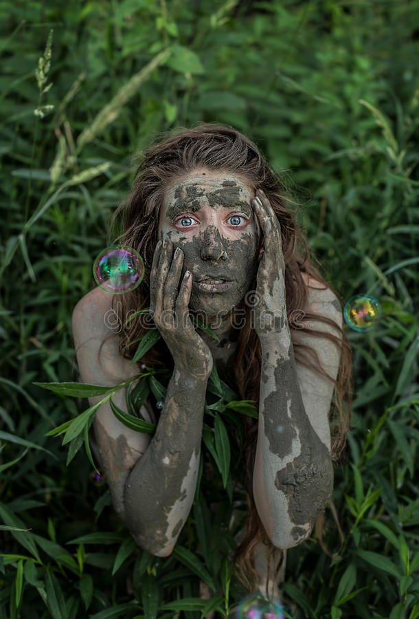 Muchacha de Muddy Amazon que oculta detrás de un arbusto en el bosque, mientras que burbujas de jabón que vuelan alrededor de ell imagen de archivo libre de regalías