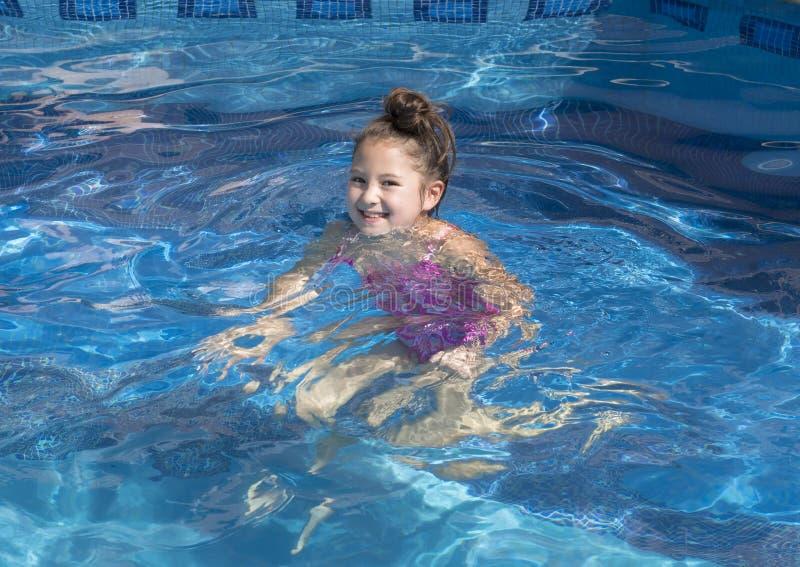 Muchacha de nueve años que pisa el agua en una piscina fotografía de archivo