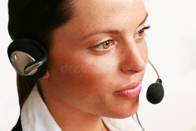 Muchacha de oficina en el receptor de cabeza imagen de archivo