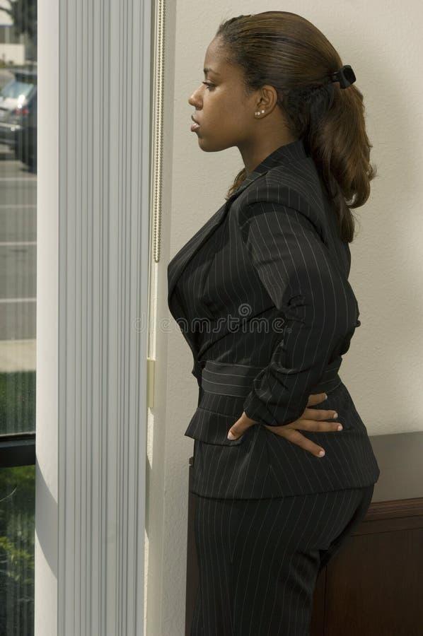 Muchacha de oficina por la ventana foto de archivo libre de regalías