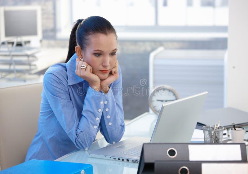 Muchacha de oficina preocupada que mira la pantalla del ordenador portátil imagen de archivo