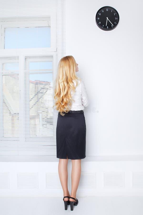Muchacha de oficina que mira en el reloj imagen de archivo