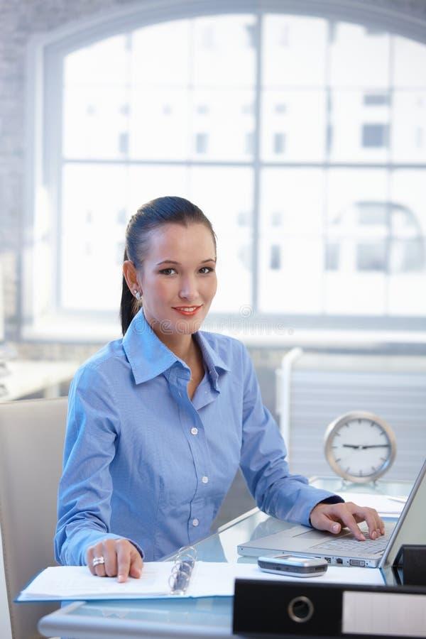 Muchacha de oficina sonriente ocupada en el escritorio imagen de archivo libre de regalías