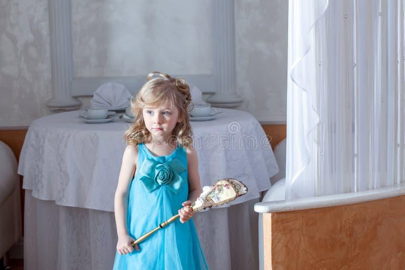 Muchacha de ojos azules confusa que presenta en vestido elegante imágenes de archivo libres de regalías