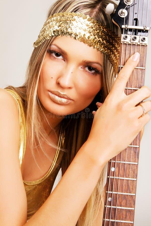 Muchacha de oro con la guitarra eléctrica foto de archivo
