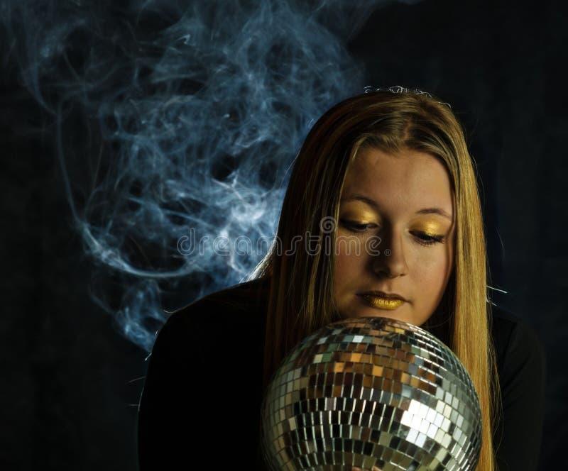 Muchacha de oro que mira en la bola de discoteca imagenes de archivo