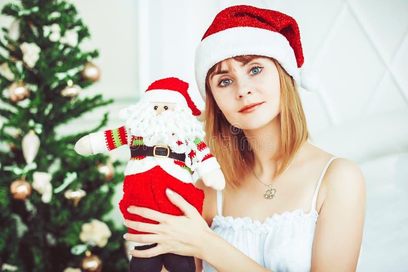 Muchacha de Papá Noel con un juguete imagen de archivo