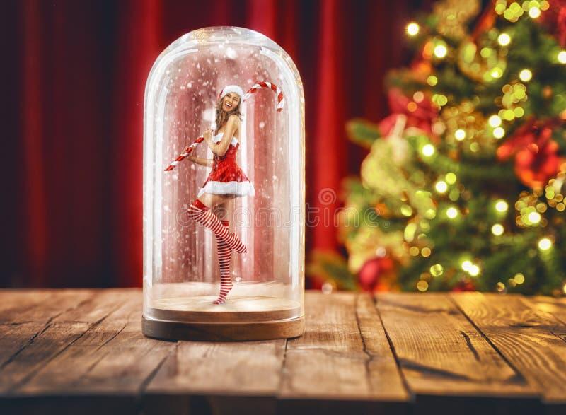 Muchacha de Papá Noel dentro de un globo de la nieve de la Navidad fotos de archivo