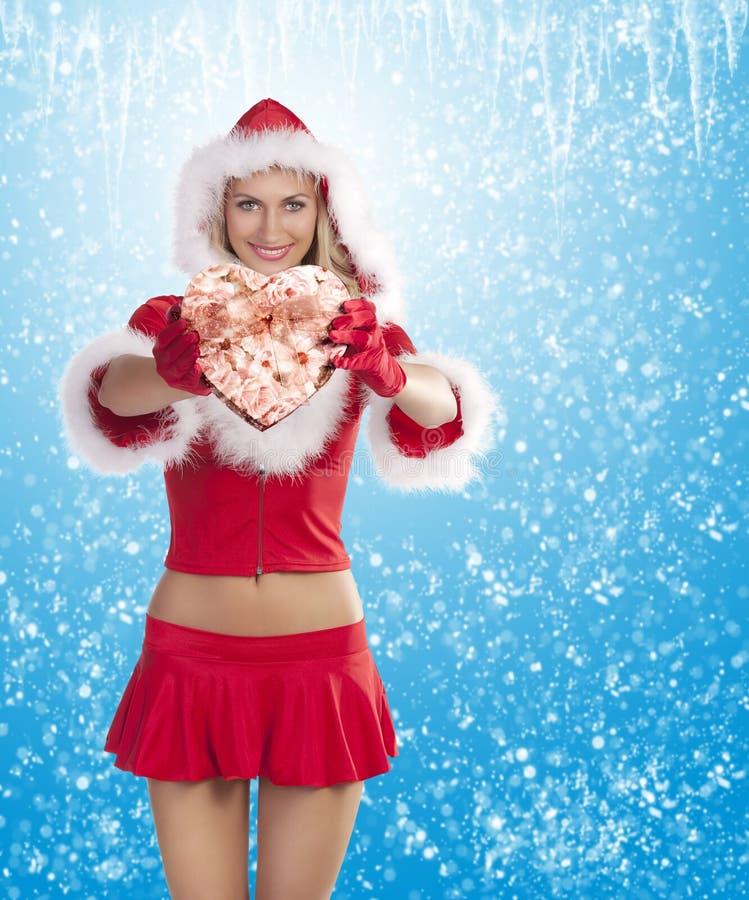 Muchacha de Papá Noel que muestra el rectángulo de regalo fotografía de archivo libre de regalías