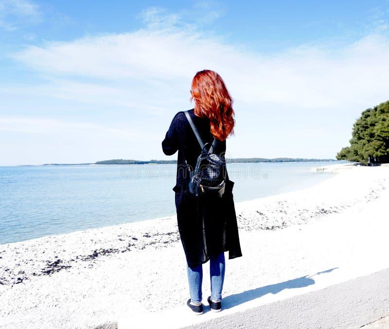 Muchacha de pelo largo del pelirrojo con el mar de observación de la mochila en un día de la sol en primavera fotografía de archivo libre de regalías