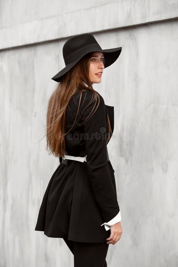 Muchacha de pelo largo delgada de moda vestida en una chaqueta elegante negra en una camisa blanca, pantalones negros y un sombre fotografía de archivo libre de regalías