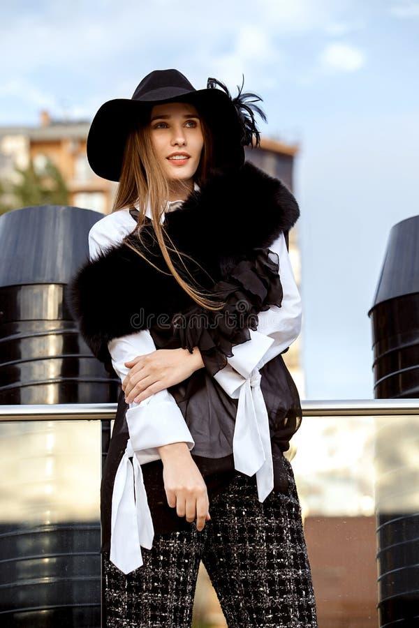 Muchacha de pelo largo delgada de moda vestida en una chaqueta elegante negra en una camisa blanca, pantalones negros y un sombre foto de archivo