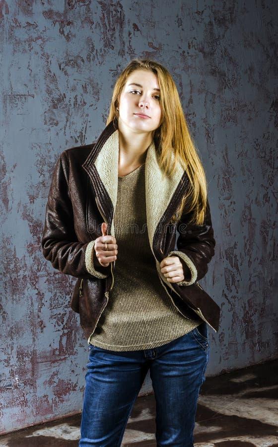 Muchacha de pelo largo joven en una chaqueta de cuero con el cuello y vaqueros de la piel fotos de archivo