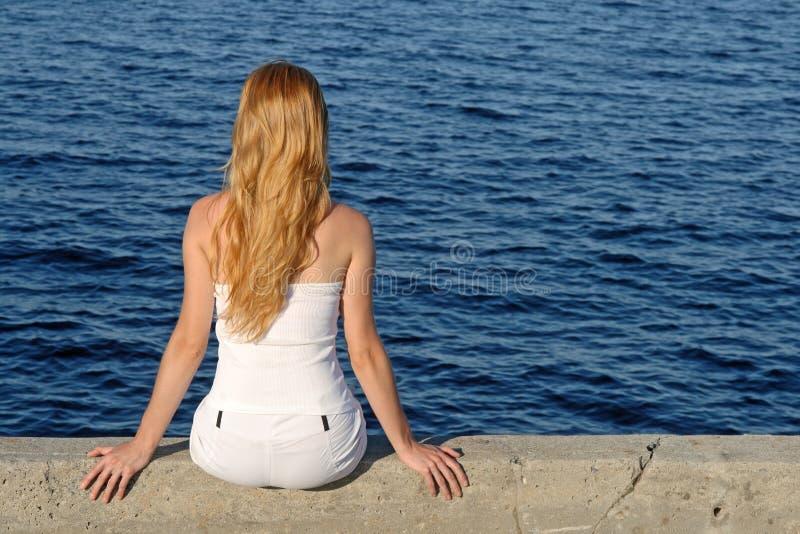 Muchacha de pelo largo que se sienta por el mar fotografía de archivo