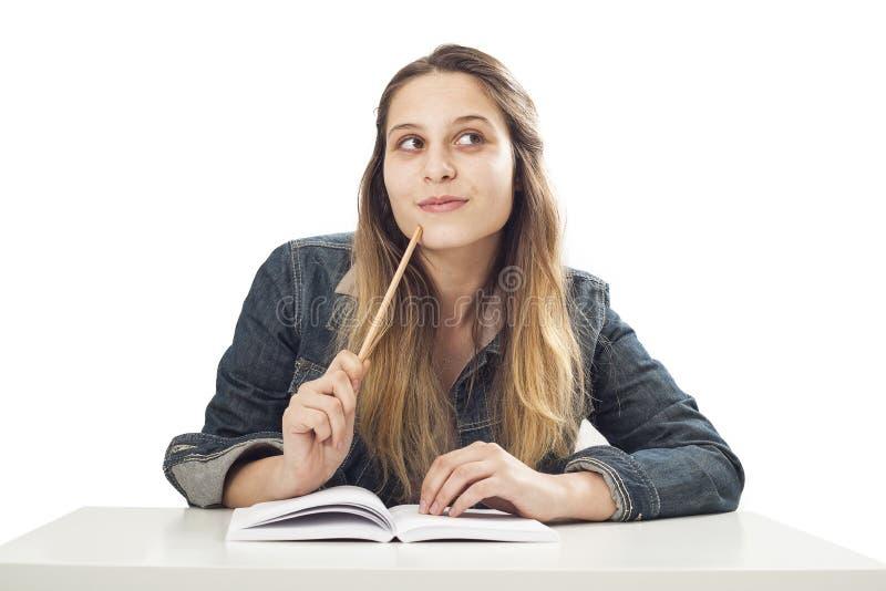 Muchacha de pensamiento del estudiante en fondo aislado foto de archivo