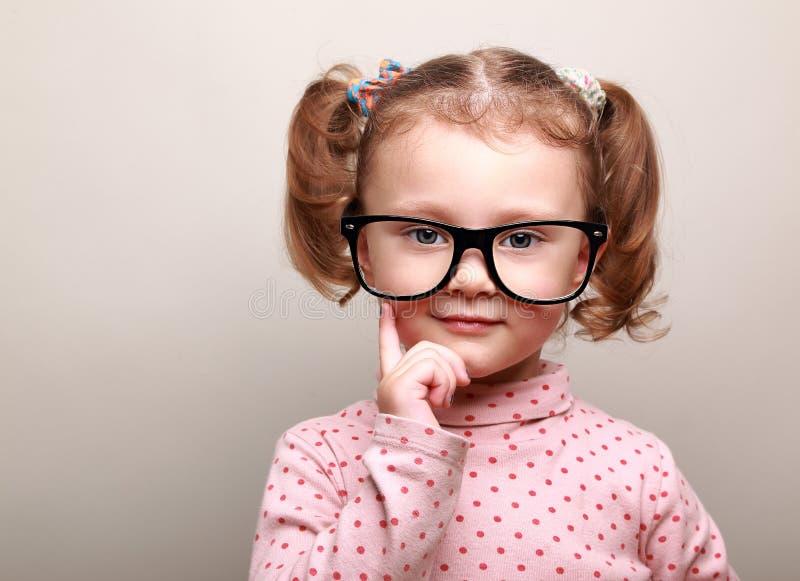 Muchacha de pensamiento del niño en los vidrios que parecen felices fotografía de archivo