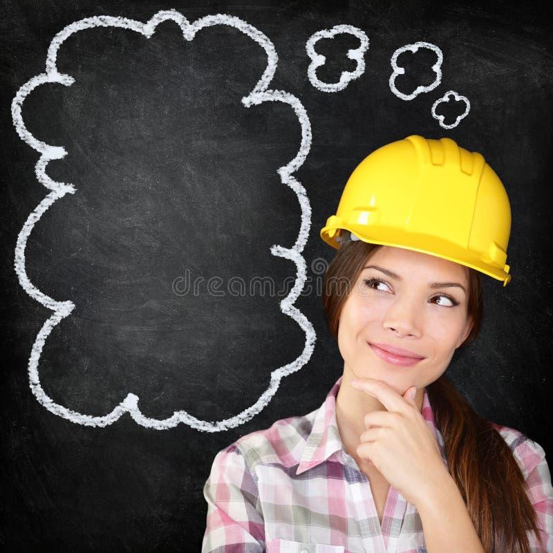 Muchacha de pensamiento del trabajador de construcción en la pizarra fotografía de archivo libre de regalías