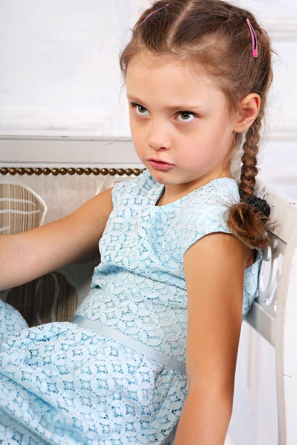 Muchacha de pensamiento enojada del niño que se sienta en el banco en vestido azul y l imagen de archivo