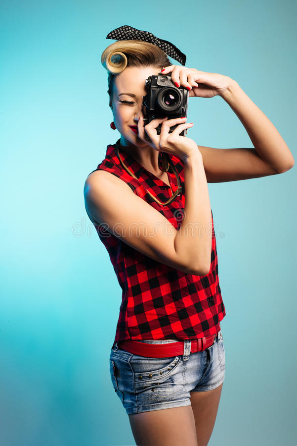 Muchacha de Pin Up que toma las fotos con la cámara del vintage fotos de archivo libres de regalías