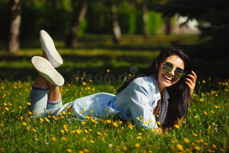 Muchacha de risa con la sonrisa feliz que miente en hierba del verano en gafas de sol circulares y ropa brillante imagenes de archivo