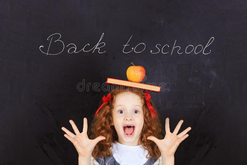 Muchacha de risa con un libro y una manzana en su cabeza Learnin fácil imagen de archivo libre de regalías