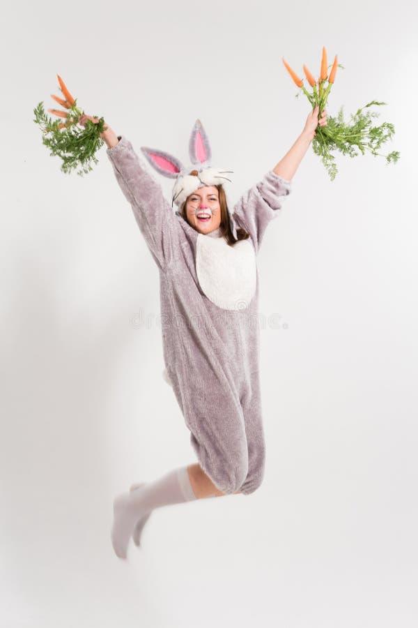 Muchacha de salto del conejo de Pascua con las zanahorias imagen de archivo libre de regalías