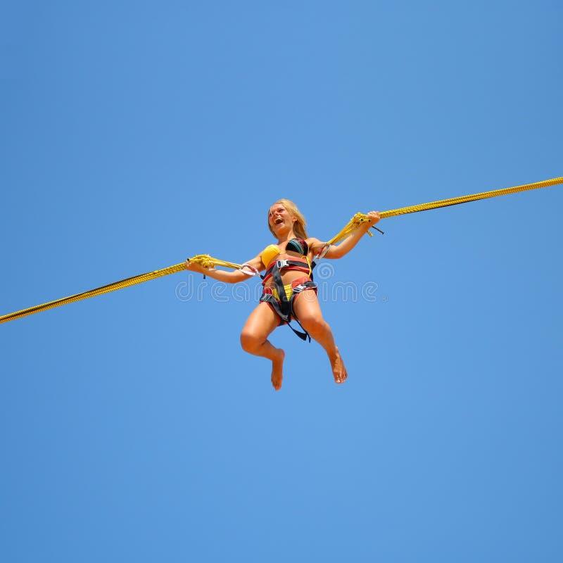 Muchacha de salto en el trampolín en el funfair imagenes de archivo