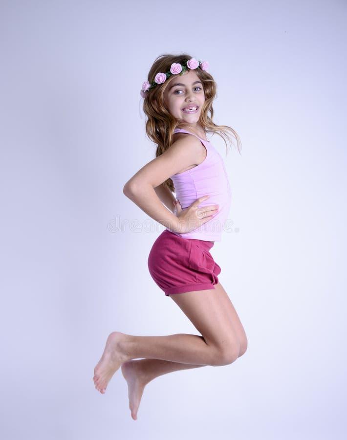 Muchacha de salto feliz con los pies desnudos y las flores en pelo fotografía de archivo libre de regalías