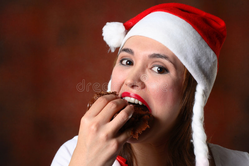 Muchacha de Santa que come la torta imagenes de archivo
