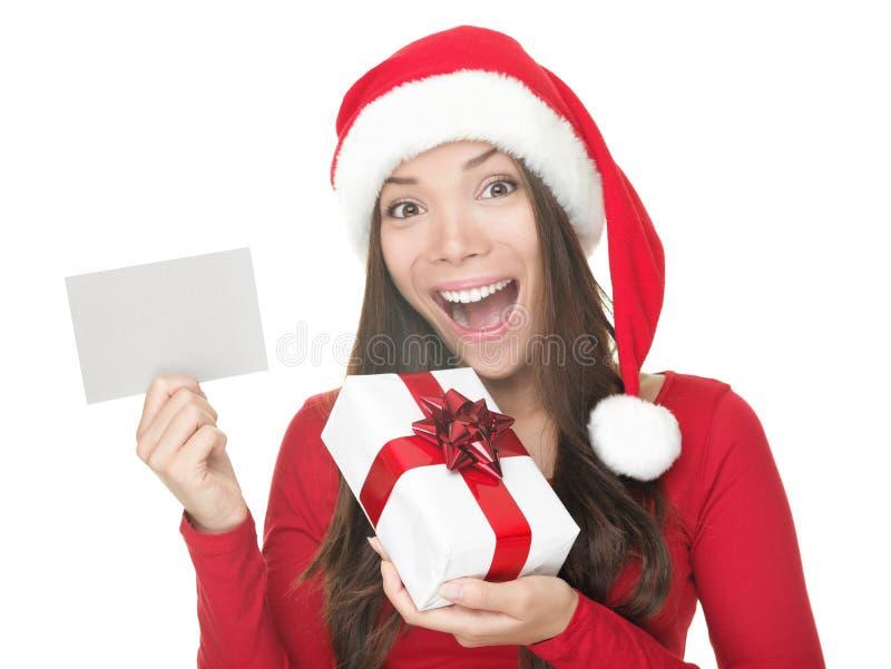 Muchacha de Santa que muestra la muestra en blanco imagen de archivo