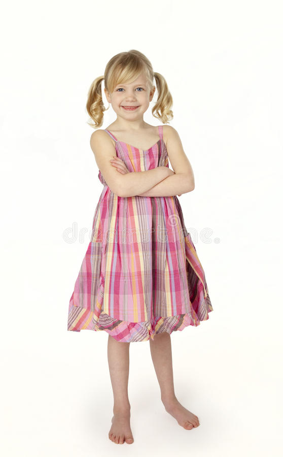 Muchacha de seis años que se coloca en el fondo blanco fotografía de archivo libre de regalías