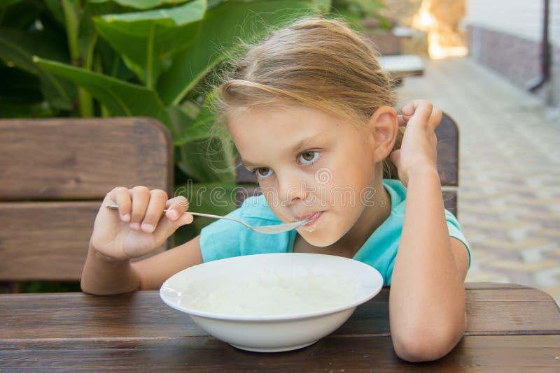 Muchacha de seis años trastornada que come lentamente las gachas de avena para el desayuno imagen de archivo