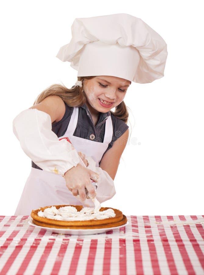 Muchacha de siete años feliz hermosa en uniforme del cocinero con shortca foto de archivo libre de regalías