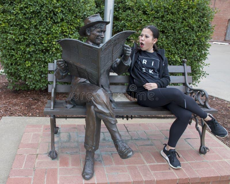 Muchacha de trece años que presenta chistoso con el bronce de la voluntad Rogers en un banco, Claremore, Oklahoma foto de archivo