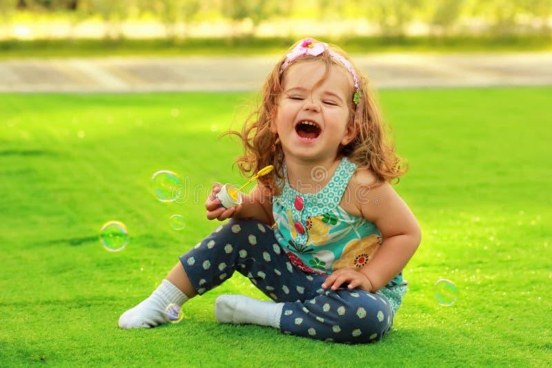 Muchacha de un año de risa que aprende soplar burbujas de jabón y que se sienta en el césped iluminado por el sol foto de archivo