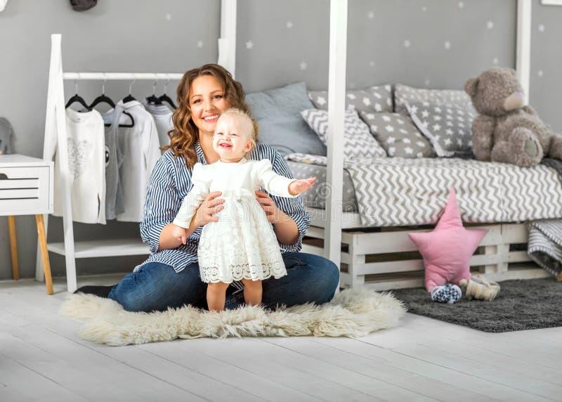 Muchacha de un año que juega cerca en el cuarto con un caballo del juguete, ska foto de archivo
