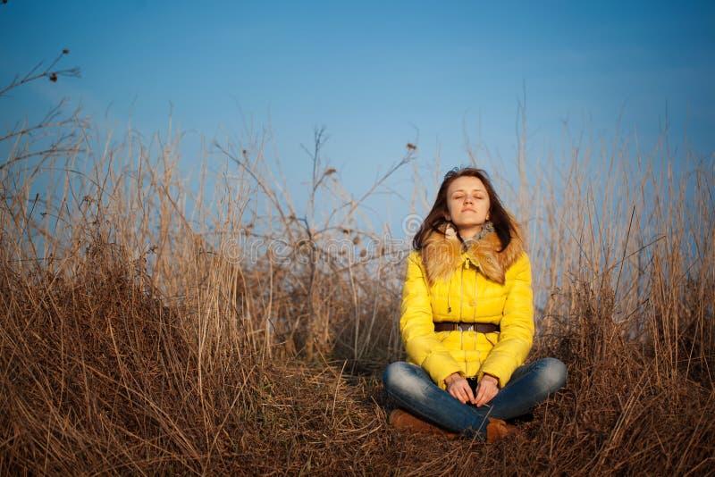 Muchacha de Youn que se sienta en hierba amarilla del otoño foto de archivo