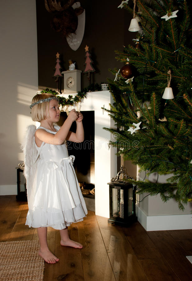 Muchacha del ángel con el oso de peluche antes del árbol de navidad foto de archivo