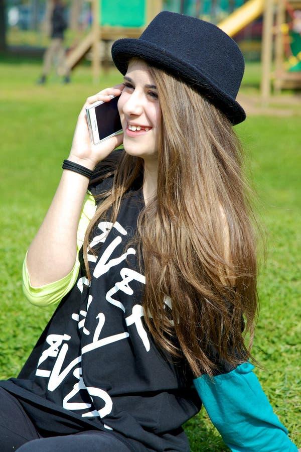 Muchacha del adolescente con el sombrero en parque que habla en el teléfono fotos de archivo libres de regalías