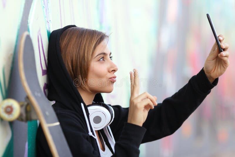 Muchacha del adolescente del patinador que toma una fotografía con la cámara elegante del teléfono foto de archivo