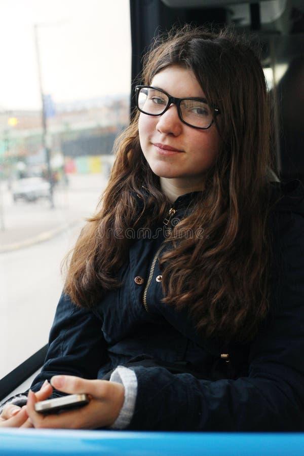 Muchacha del adolescente en el autobús en vidrios de la corrección de la vista foto de archivo libre de regalías