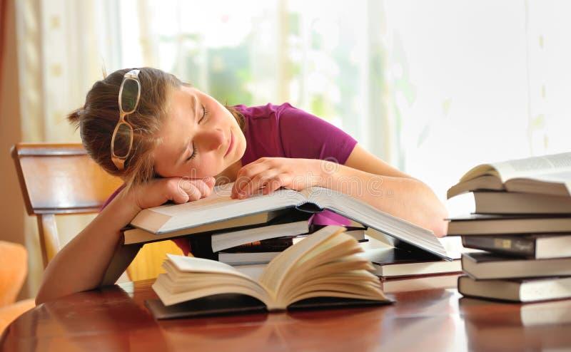 Muchacha del adolescente que duerme en los libros foto de archivo