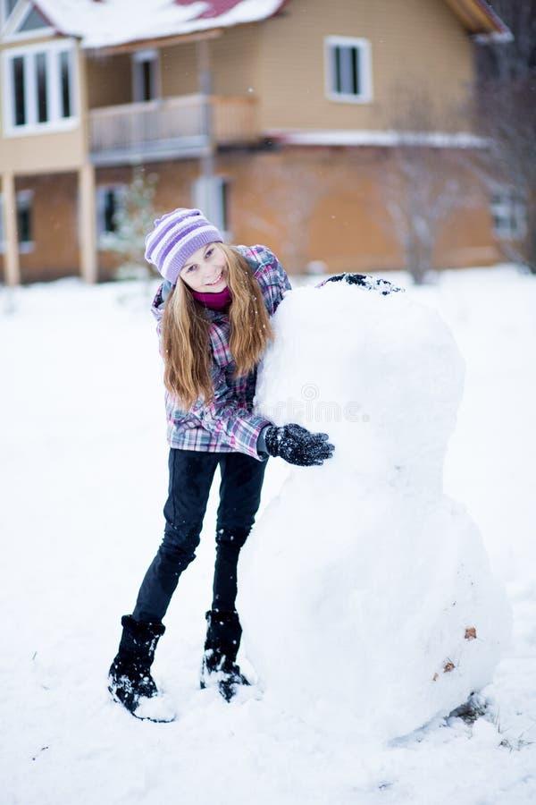 Muchacha del adolescente que hace el muñeco de nieve al aire libre delante de casa fotos de archivo libres de regalías