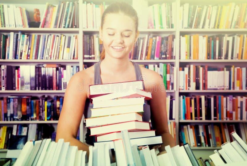 Muchacha del adolescente que sostiene una pila de libros en una librería fotos de archivo