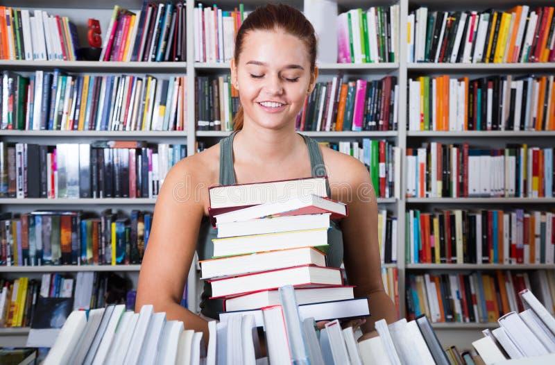 Muchacha del adolescente que sostiene una pila de libros en una librería fotografía de archivo