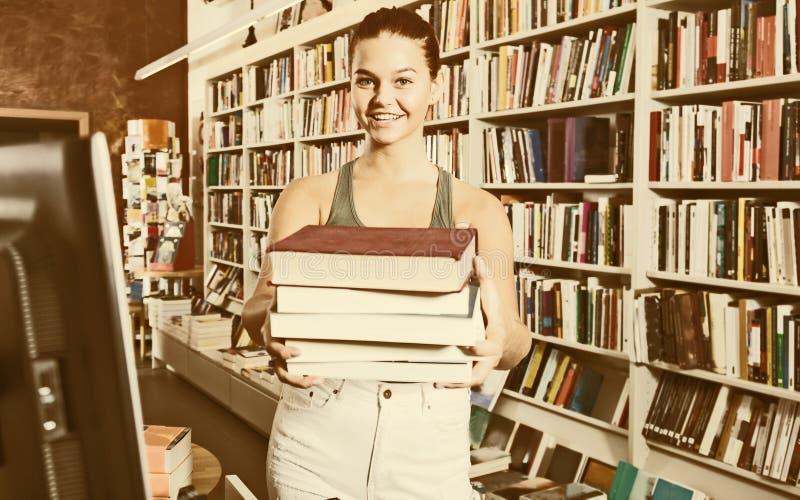 Muchacha del adolescente que sostiene una pila de libros en una librería imagenes de archivo