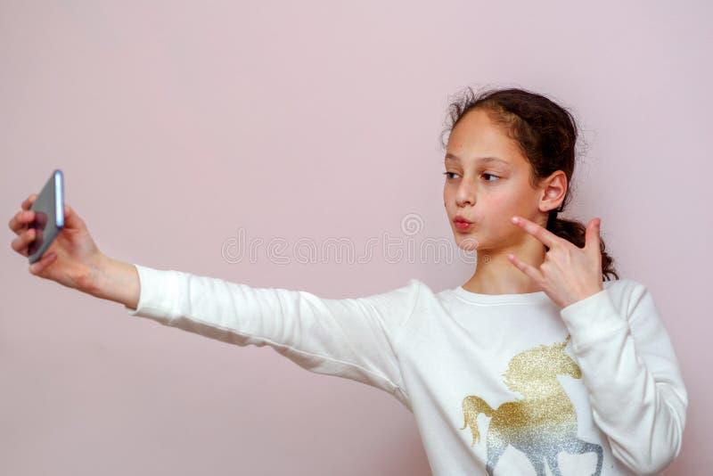 Muchacha del adolescente que toma el selfie con su tel?fono celular en fondo rosado imagen de archivo