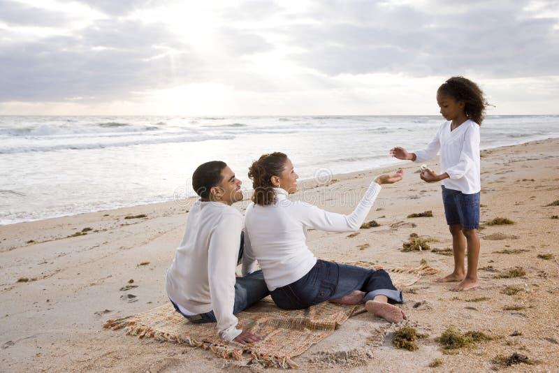 Muchacha del African-American con los padres en la playa foto de archivo libre de regalías